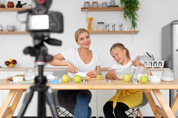 テーブルでミディアムショットの女性と女の子