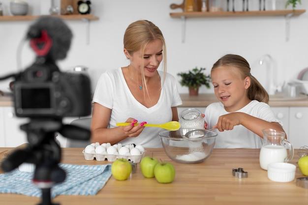 キッチンでミディアムショットの女性と女の子