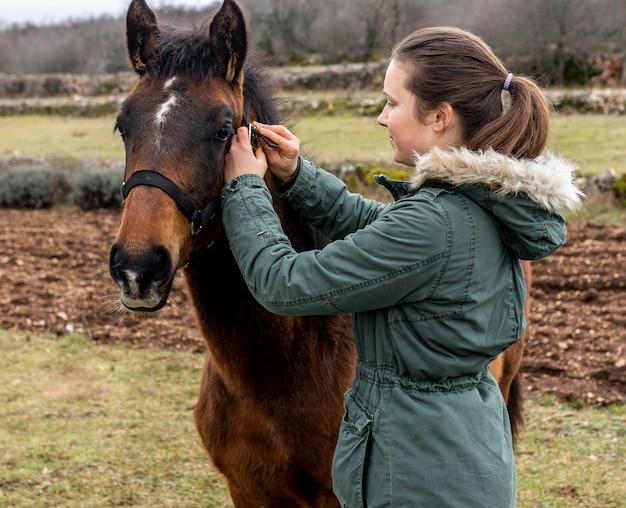 ミディアムショットの女性と屋外の馬