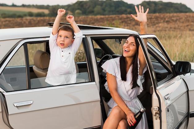 車の中でミディアムショットの女性と子供