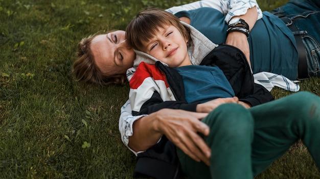 ミディアムショットの女性と草の上の子供