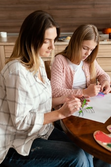 Средний план женщина и ребенок рисуют бабочек
