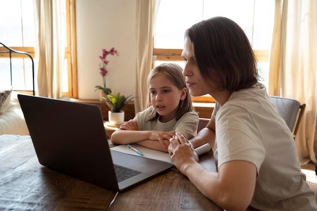 Среднего выстрела женщина и ребенок с ноутбуком