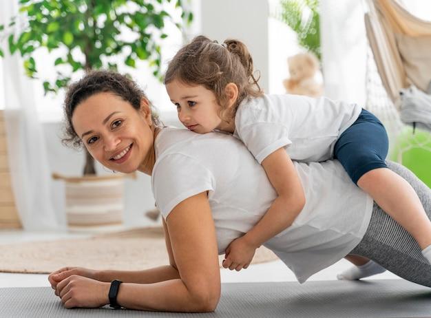 ミディアムショットの女性と子供が運動