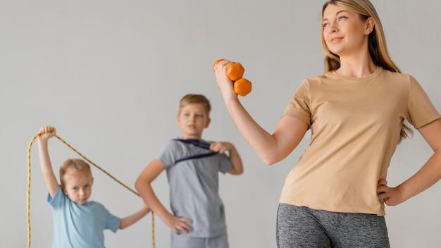 Средний выстрел женщина и дети, тренирующиеся