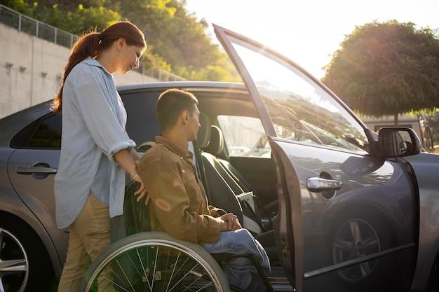 Средний снимок женщина и мужчина в инвалидной коляске