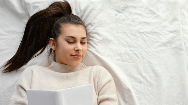 Donna del colpo medio a letto con il libro