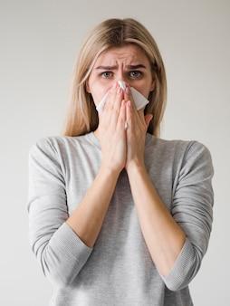 Medium shot woman blowing nose