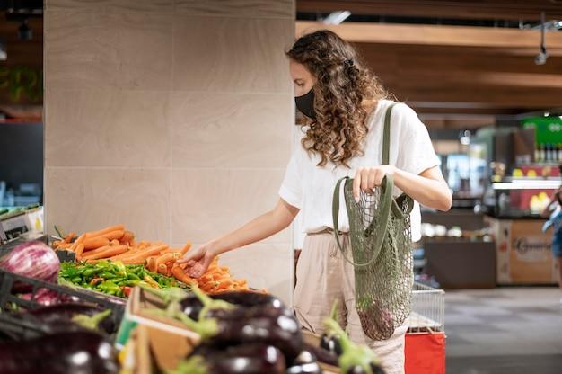 Donna di tiro medio che compra verdura