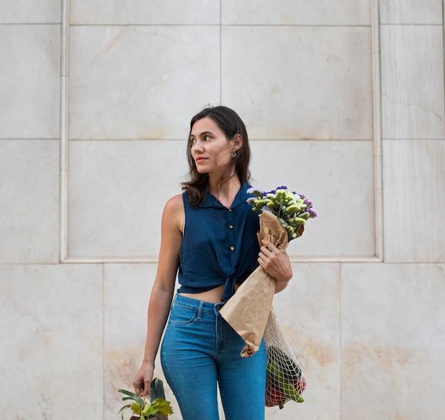 Donna a tiro medio che porta borse e fiori