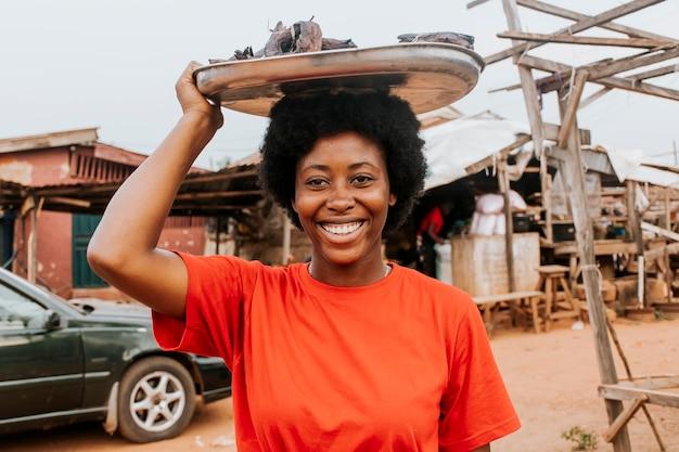 Medium shot woman carrying food on head
