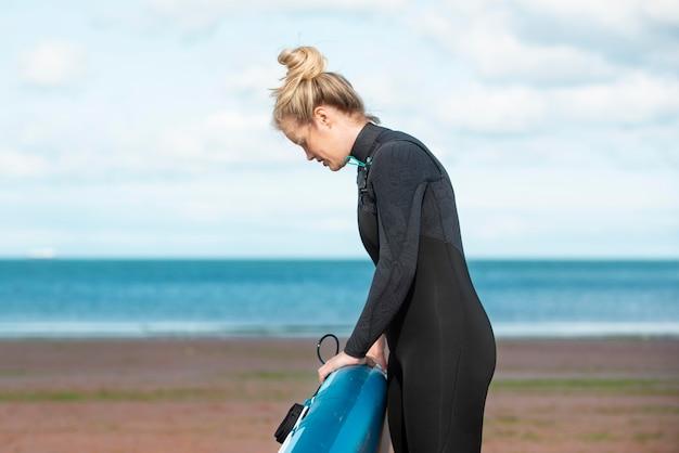Medium shot woman carrying paddleboard