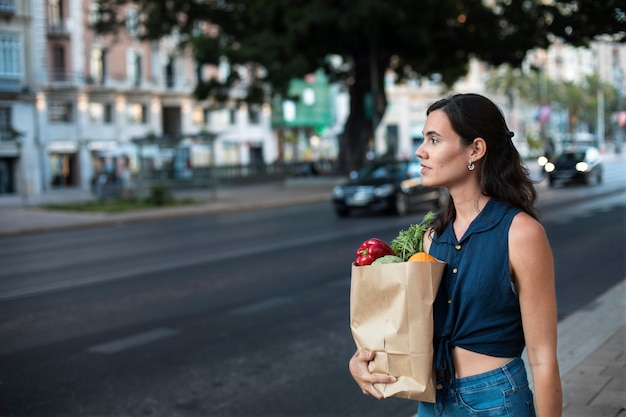 Medium shot woman carrying paper bag