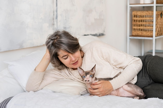 Medium shot woman and cat in bed