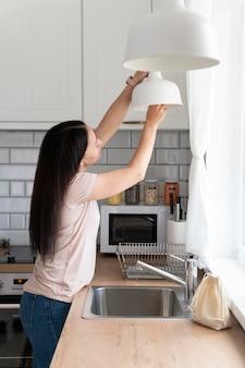 Средний снимок женщины, меняющей лампочку