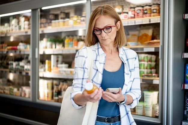 Colpo medio donna che controlla il prodotto