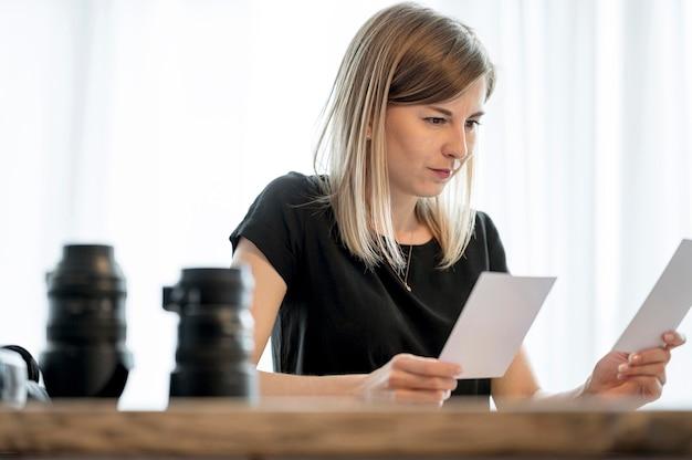 Medium shot of woman choosing between photos