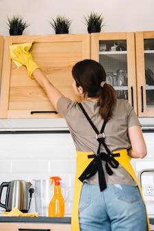 Medium shot woman cleaning cabinet