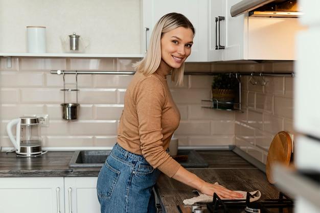 Средние кадры женщина чистит столешницу Premium Фотографии
