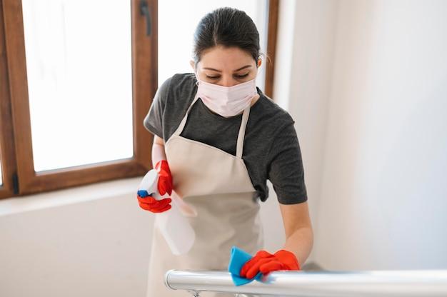 Medium shot woman cleaning railing