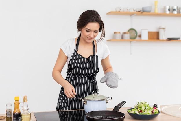 屋内で調理するミディアムショットの女性