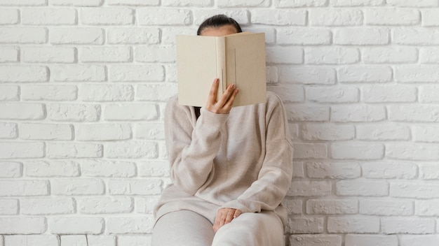 Medium shot woman covering face with book
