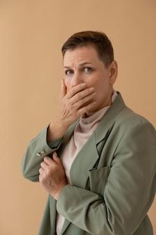 Женщина среднего выстрела прикрывает рот
