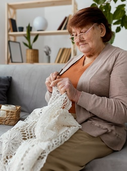 Medium shot woman crocheting on couch