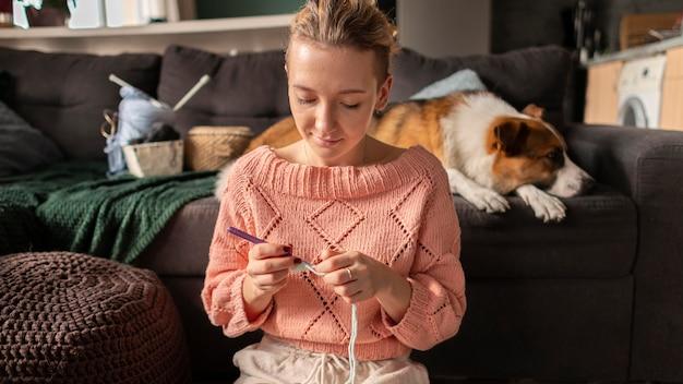 Medium shot woman crocheting with dog