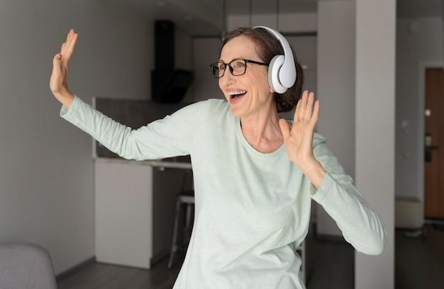 ヘッドフォンで踊るミディアムショットの女性