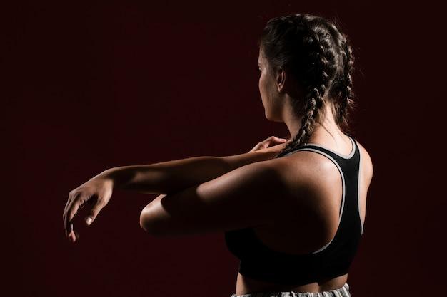 Medium shot woman in dark background from behind shot