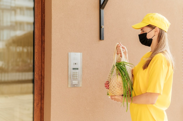 Женщина среднего кадра, доставляющая сетку для фруктов
