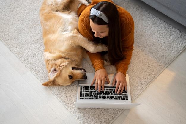 Medium shot woman and dog on floor
