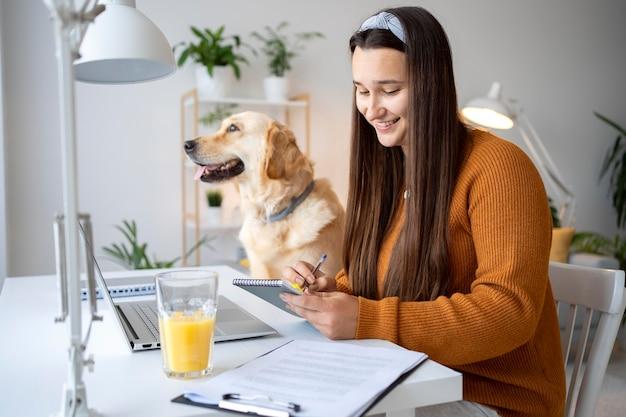 Medium shot woman and dog at home