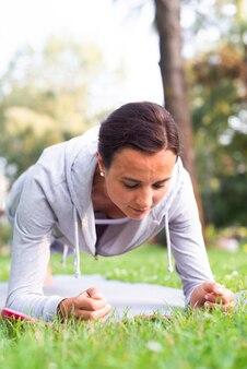 Medium shot woman doing planks outdoors