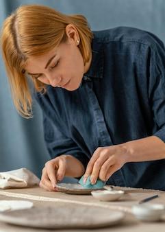 Donna del colpo medio che fa ceramiche