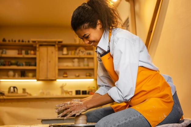 Женщина среднего кадра делает керамику