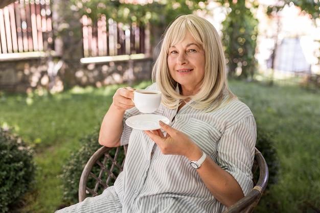 ミディアムショットの女性がコーヒーを飲む