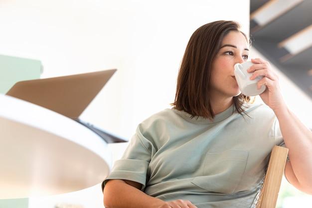 コーヒーを飲むミディアムショットの女性