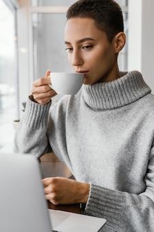 カップから飲むミディアムショットの女性