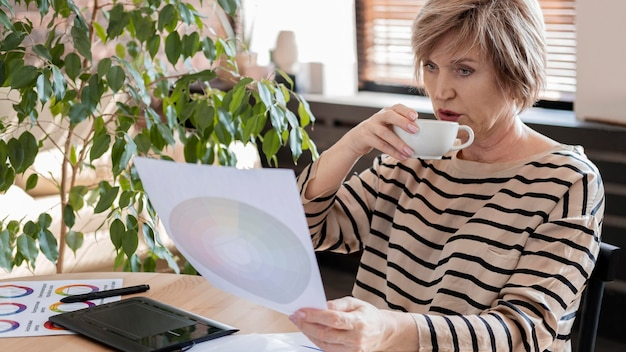 Donna del colpo medio che beve dalla tazza