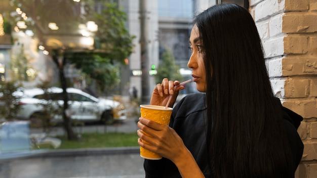 Colpo medio donna che beve succo di frutta