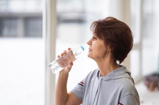 Acqua potabile della donna del colpo medio