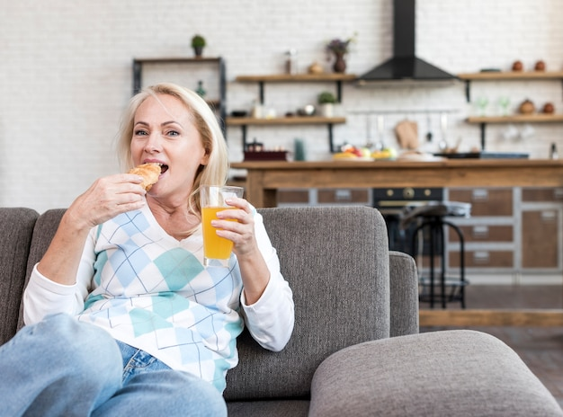 Medium shot woman eating on the couch