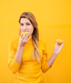 Donna del colpo medio che mangia frutta