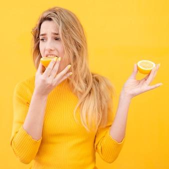 Donna del primo piano che mangia limone