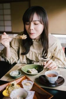 ミディアムショットの女性が食べる