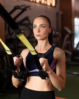 Medium shot woman exercising at gym