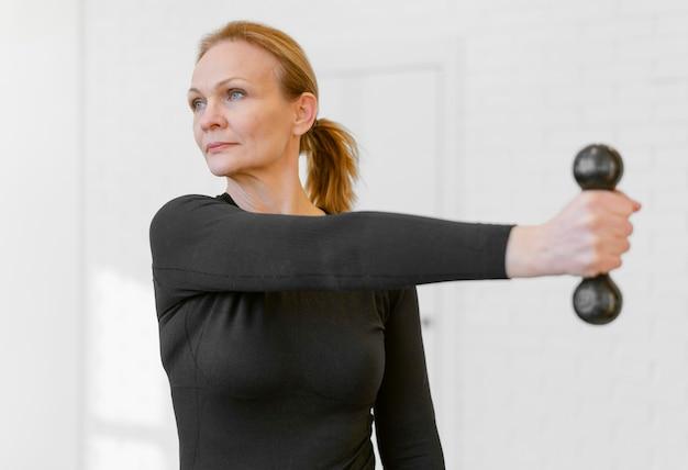 Женщина среднего выстрела, тренирующаяся с гантелями