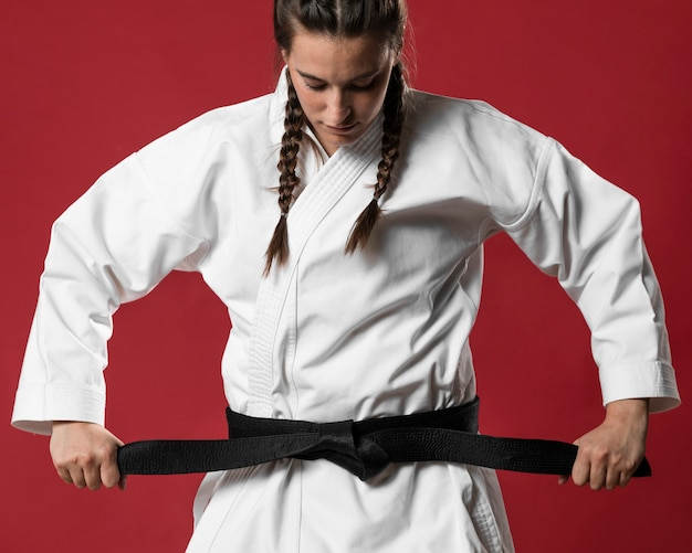 Medium shot of woman fighter straighten her belt